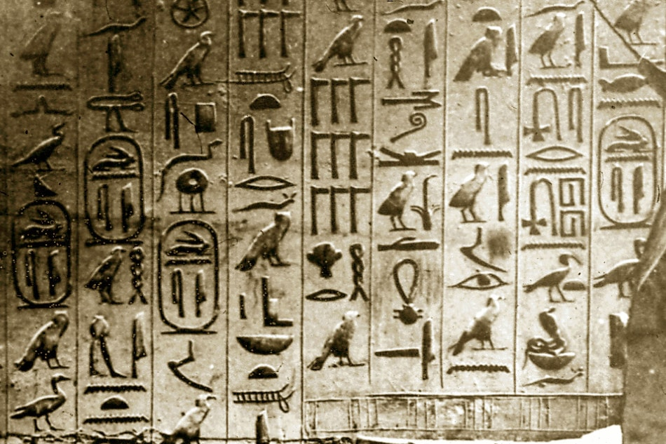 Egyptian hieroglyphs carved into a stone wall